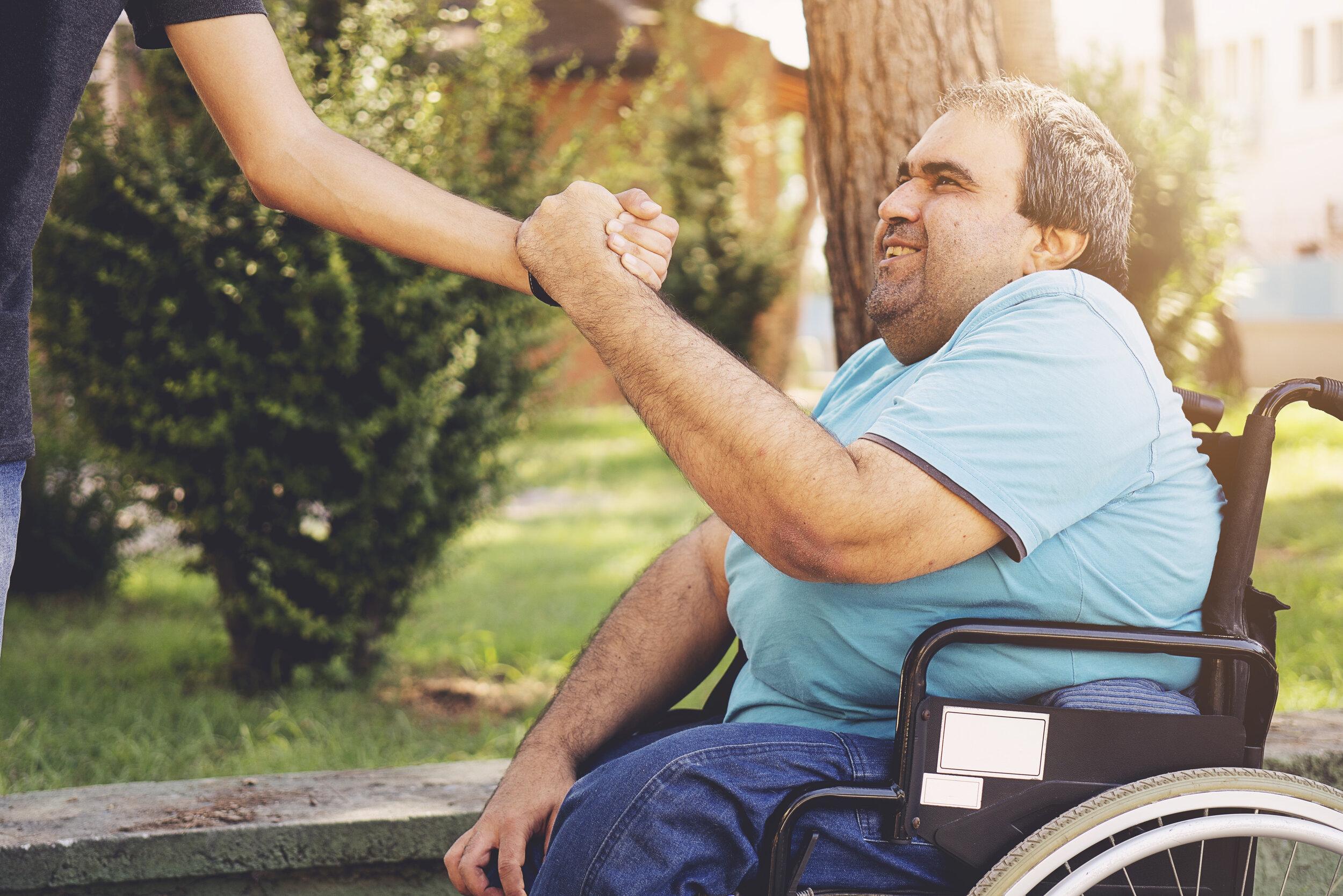 man in wheelchair getting help