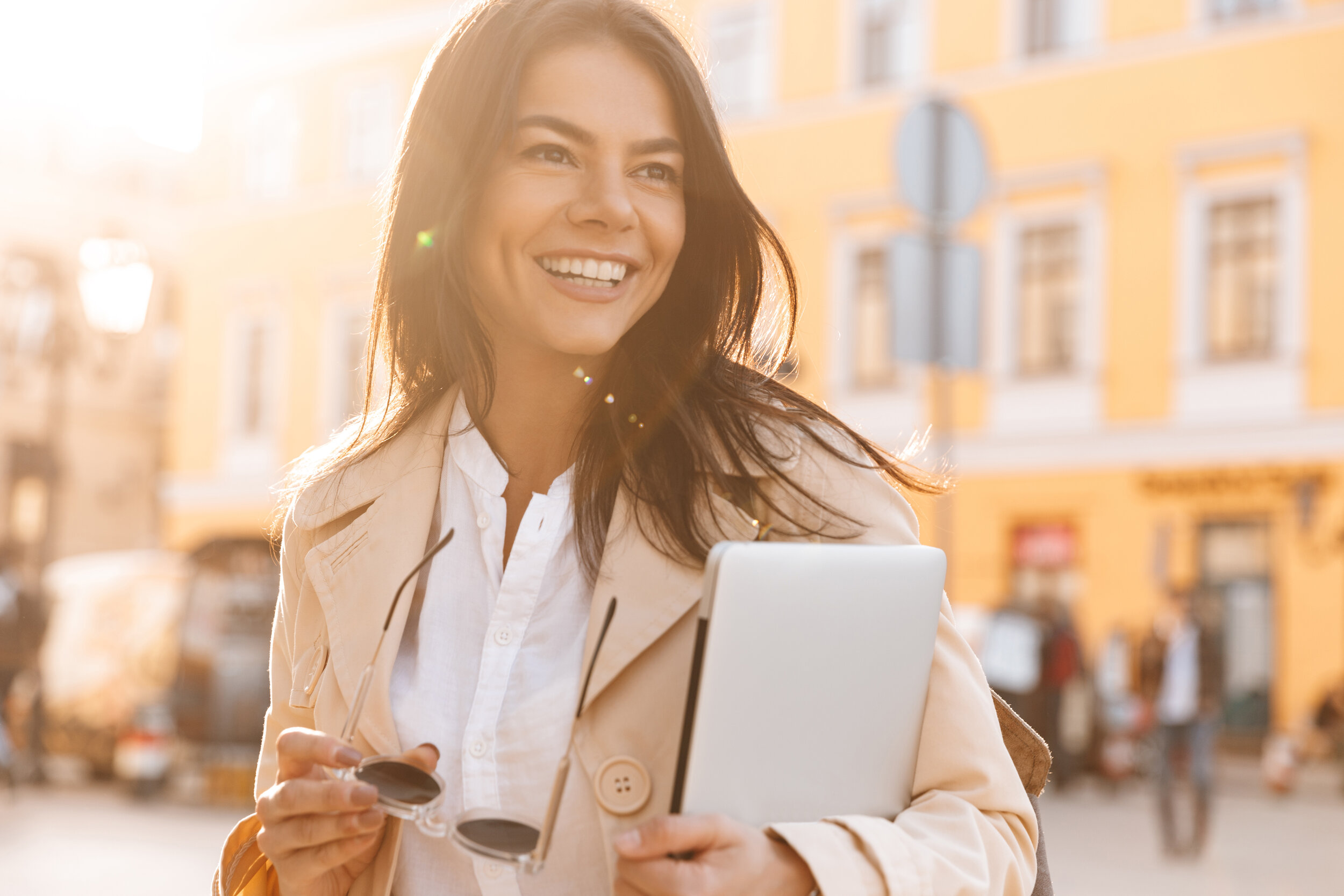 woman smiling outside with laptop